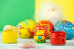Wielkanocni jajka na multicolor drewnianym tle z kurczakiem, farbami i muśnięciem dziecka, fotografia royalty free