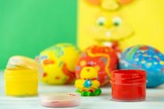 Wielkanocni jajka na multicolor drewnianym tle z kurczakiem, farbami i muśnięciem dziecka, obrazy royalty free