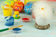 Wielkanocni jajka na multicolor drewnianym tle z kurczakiem, farbami i muśnięciem dziecka, obrazy stock