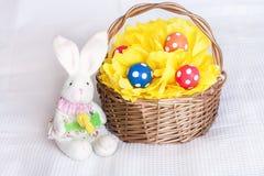 Wielkanocni jajka na pomponie w kosza i zabawki króliku na w kratkę whi Zdjęcia Stock