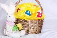 Wielkanocni jajka na pomponie w kosza i zabawki króliku na w kratkę whit Zdjęcie Stock