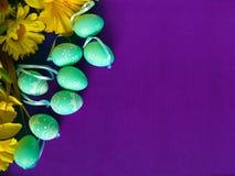 Wielkanocni jajka na purpurowym jedwabiu z żółtymi kwiatami, obrazy royalty free