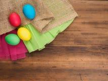 Wielkanocni jajka na starym brown drewnianym tle z borlap i zielonym papierem odgórny widok, horyzontalny Egzamin próbny up dla t Zdjęcie Royalty Free