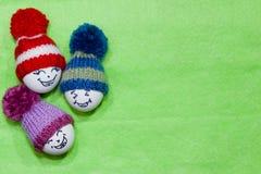 Wielkanocni jajka na zieleni czującej Emoticons w trykotowym kapeluszu z pom-pom Zdjęcia Stock