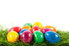 Wielkanocni jajka na zielonych gras odosobnionym jedzeniu Obrazy Royalty Free