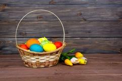 Wielkanocni jajka w łozinowego kosza, czerwieni i koloru żółtego tulipanach na drewnianych deskach, obraz stock