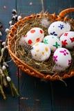 Wielkanocni jajka w łozinowego kosza i wierzby gałąź na drewnianym stole Obraz Royalty Free