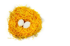 Wielkanocni jajka w żółtym słomy gniazdeczku odizolowywającym na białym tle Zdjęcia Stock