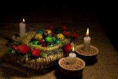 Wielkanocni jajka w drewnianym koszu z Wielkanocnymi świeczkami Zdjęcie Stock