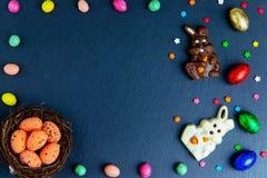 Wielkanocni jajka w gniazdeczku, czekoladowi jajka i cukierki, Odg?rny widok na kamienia stole z przestrzeni? dla tw?j powitanie  zdjęcia stock
