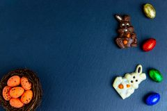 Wielkanocni jajka w gniazdeczku, czekoladowi jajka i cukierki, Odg?rny widok na kamienia stole z przestrzeni? dla tw?j powita? zdjęcie royalty free