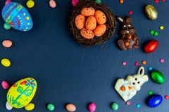 Wielkanocni jajka w gniazdeczku, czekoladowi jajka i królik, Odgórny widok na kamienia stole z przestrzenią dla twój powitani obrazy stock