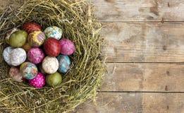 Wielkanocni jajka w gniazdeczku na nieociosanym drewnianym tle zdjęcie stock