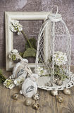 Wielkanocni jajka w klatce, skaczą biali kwiaty, przepiórek jajka, biali króliki Fotografia Stock