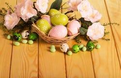 Wielkanocni jajka w kosza i liczby ziele, kwiaty, cukierek, faborek zdjęcia royalty free