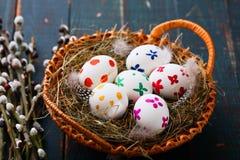 Wielkanocni jajka w kosza i wierzby gałąź na drewnianym stole Obraz Stock