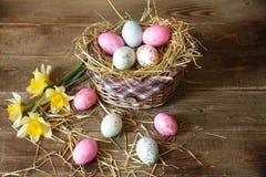 Wielkanocni jajka w koszu dekorowali z słomą i narcyzem na drewnianym nieociosanym tle obraz royalty free