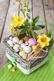 Wielkanocni jajka w koszu na zieleni paskowali płótno Zdjęcie Stock