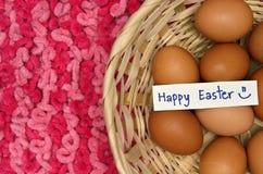 Wielkanocni jajka w koszu z notatką na różowym tkaniny tle obraz stock