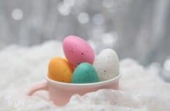 Wielkanocni jajka w różowej filiżance na biel koronce, obraz stock