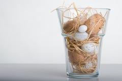 Wielkanocni jajka w szklanej wazie na stole Fotografia Royalty Free