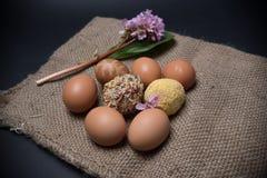 Wielkanocni jajka z jajkami na jutowym tle i kwiatach Zdjęcia Royalty Free