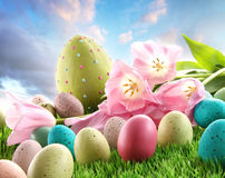Wielkanocni jajka z tulipanami w trawie Zdjęcia Royalty Free