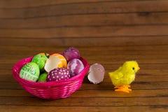 Wielkanocni kolorowi jajka w kosza i zabawki kurczaku Obrazy Royalty Free