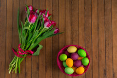 Wielkanocni kolorowi malujący jajka i wiązka tulipany Zdjęcia Royalty Free