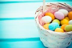 Wielkanocni kolorowi słodcy jajka w białym koszu na turkusowym drewnianym tle Copyspace Zdjęcia Stock