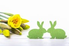 Wielkanocni króliki i daffodils na drewnianym tle i Fotografia Stock