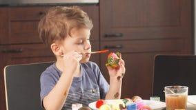 Wielkanocny świętowania pojęcie Szczęśliwa chłopiec dekoruje Easter jajka dla wakacje zbiory