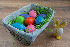 Wielkanocny łozinowy kosz z barwionymi jajkami i małym królikiem na drewnianej desce Fotografia Royalty Free