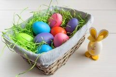 Wielkanocny łozinowy kosz z barwionymi jajkami i małym królikiem na drewnianej desce Zdjęcia Stock