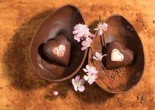 Wielkanocny czekoladowy jajko z niespodzianką dwa serca dekorującego, kropiącą z kakaowym proszkiem i migdałowym okwitnięciem Fotografia Royalty Free