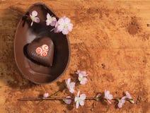 Wielkanocny czekoladowy jajko z niespodzianką kropiącą z kakaowym proszkiem i towarzyszącą z migdałowym okwitnięciem dekorujący s Zdjęcie Royalty Free