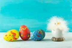 Wielkanocny dziecko kurczak obok jajek na błękitnym drewnianym tle obraz royalty free