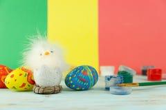 Wielkanocny dziecko kurczak obok jajek na multicolor drewnianym tle z farbami i muśnięciem zdjęcie stock