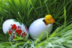 Wielkanocny jajko i mały zabawkarski kaczątko w trawie Zdjęcia Stock