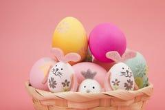 Wielkanocny jajko z różowym tematem w koszu jajko dekoruje jak śliczny królik bawić się z innym królikiem na różowym tle, obrazy stock