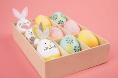 Wielkanocny jajko z różowym tematem w pudełku jajko dekoruje jak śliczny królik bawić się z innym królikiem na różowym tle, zdjęcia stock