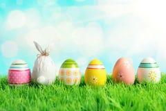 Wielkanocny jajko zawijający w papierze w formie królika z kolorowymi Wielkanocnymi jajkami na zielonej trawie Wiosna wakacji poj zdjęcia stock