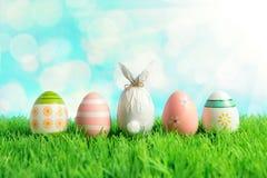 Wielkanocny jajko zawijający w papierze w formie królika z kolorowymi Wielkanocnymi jajkami na zielonej trawie Wiosna wakacji poj fotografia stock