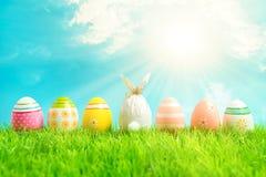 Wielkanocny jajko zawijający w papierze w formie królika z kolorowymi Wielkanocnymi jajkami na zielonej trawie Wiosna wakacji poj zdjęcie stock