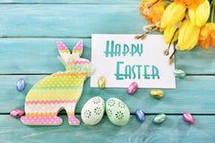 Wielkanocny kartka z pozdrowieniami z kolorowym królikiem, jajkami i tulipanami, Fotografia Stock
