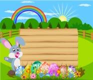 Wielkanocny królik trzyma kosz Wielkanocni jajka z Wielkanocnymi jajkami i drewno znakiem wsiada Fotografia Royalty Free