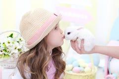 Wielkanocny pojęcia i rodziny wakacje! Śliczna dziewczyna całuje Wielkanocnego królika Wielkanocny kolorowy wystrój Dzieci bawią  fotografia royalty free