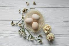 Wielkanocny skład z jajkami i wysuszonymi fiołkowymi płatkami kwiaty Zdjęcia Stock