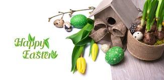 Wielkanocny sztandar z birdhouse, żółtymi tulipanami i Wielkanocnymi jajkami, zdjęcie stock