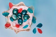 Wielkanocny tło z jajkami dekorował w błękitnym, turkusie i złocie w gniazdeczku z kolorowymi piórkami, Odgórny widok kosmos kopi zdjęcia royalty free